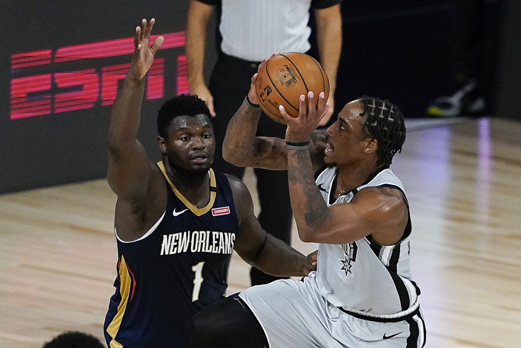 San Antonio Spurs' DeMar DeRozan, right, goes up for a shot against New Orleans Pelicans' Zion Williamson (1) during the second half of an NBA basketb...