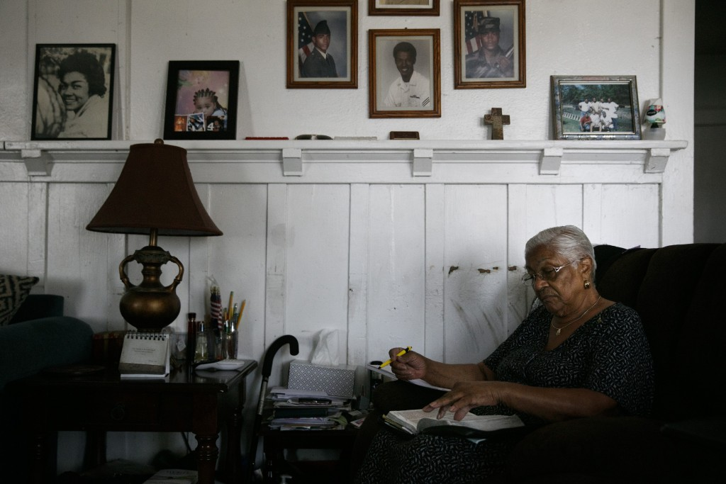 Lavarn Young, 81, reads her bible in the living room of her home as framed photos of herself, far left, and relatives adorn a wall Tuesday, July 14, 2...