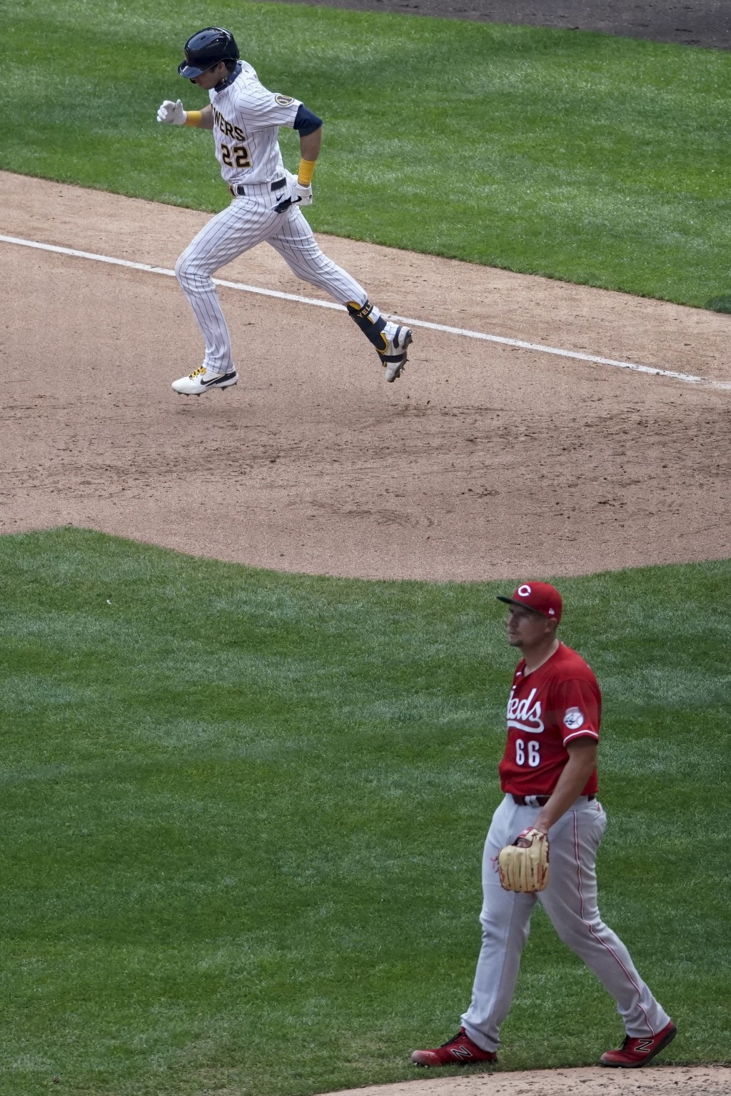 Cincinnati Reds reliever Joel Kuhnel looks back after Milwaukee Brewers' Christian Yelich hits a home run during the seventh inning of a baseball game...