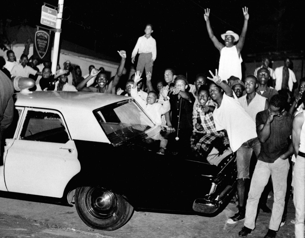 FILE - In this Aug. 12, 1965, file photo, demonstrators push against a police car in the Los Angeles area of Watts. Watts has been associated with an ...