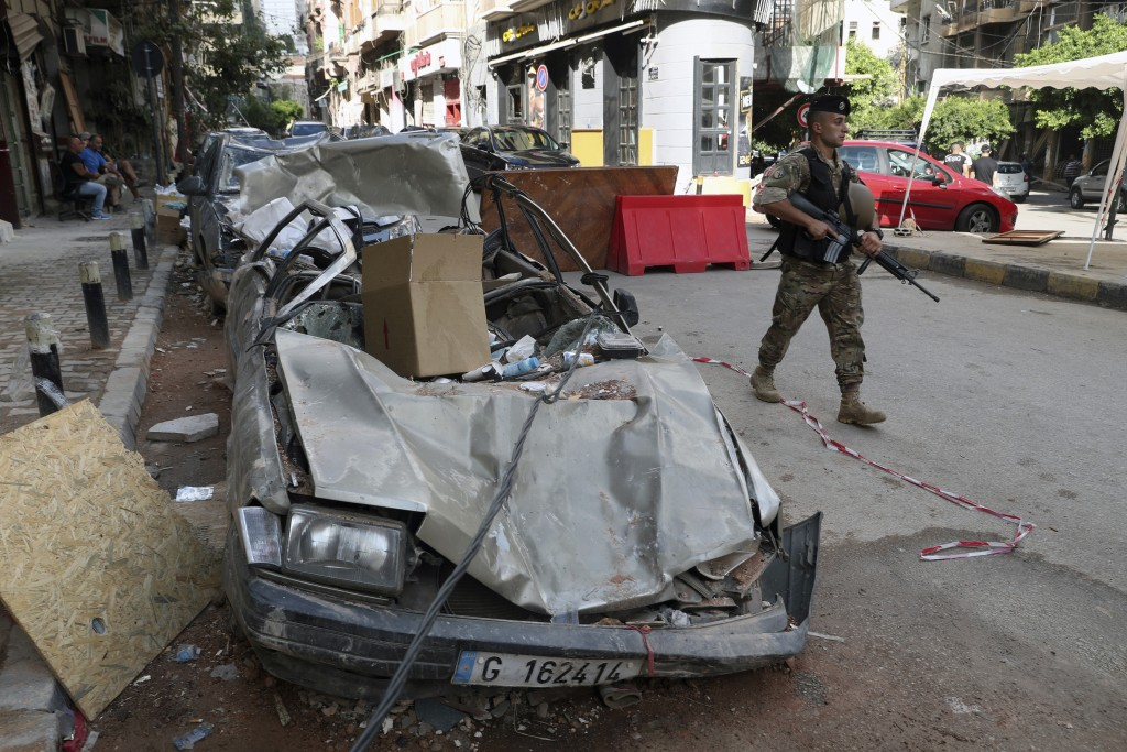 A soldier walks past damaged vehicles, Monday, Aug. 10, 2020, in Beirut, Lebanon, near the site of last week's explosion that hit the city's seaport. ...