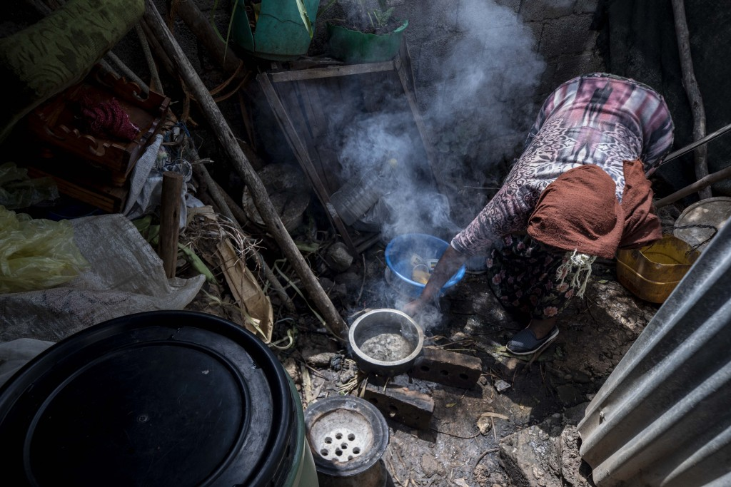 Mother of two Amsale Hailemariam, a domestic worker who lost work because of the coronavirus, prepares food for her family in her small tent in the ca...