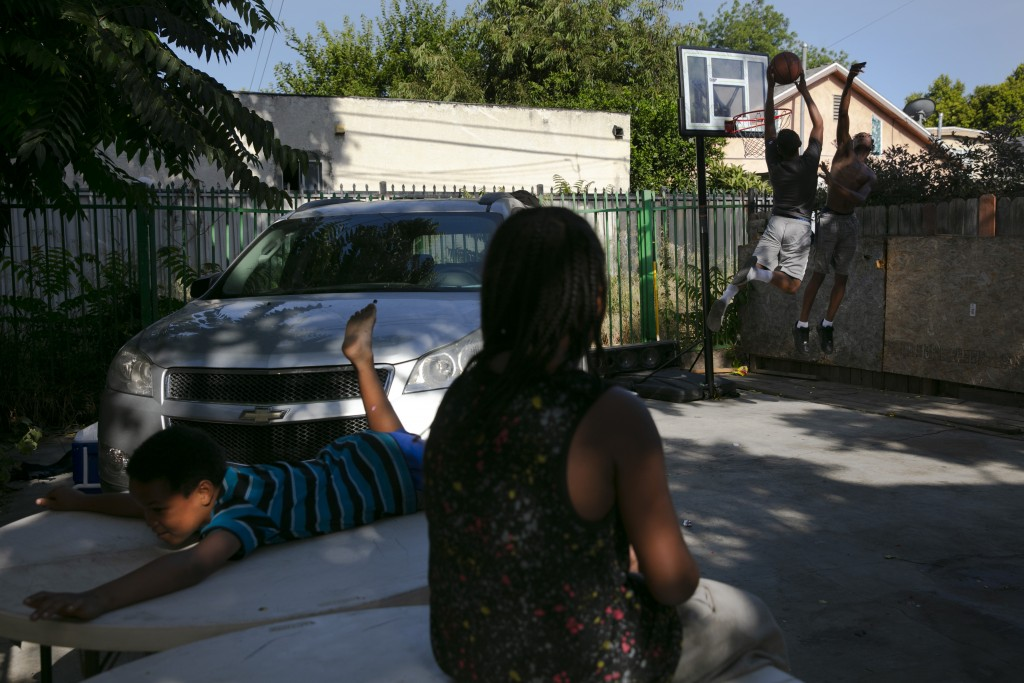 Aiden Figueroa, foreground, watches as James Posey III, far right, and Aiden's brother, Darius play basketball in the backyard of their home in the Wa...