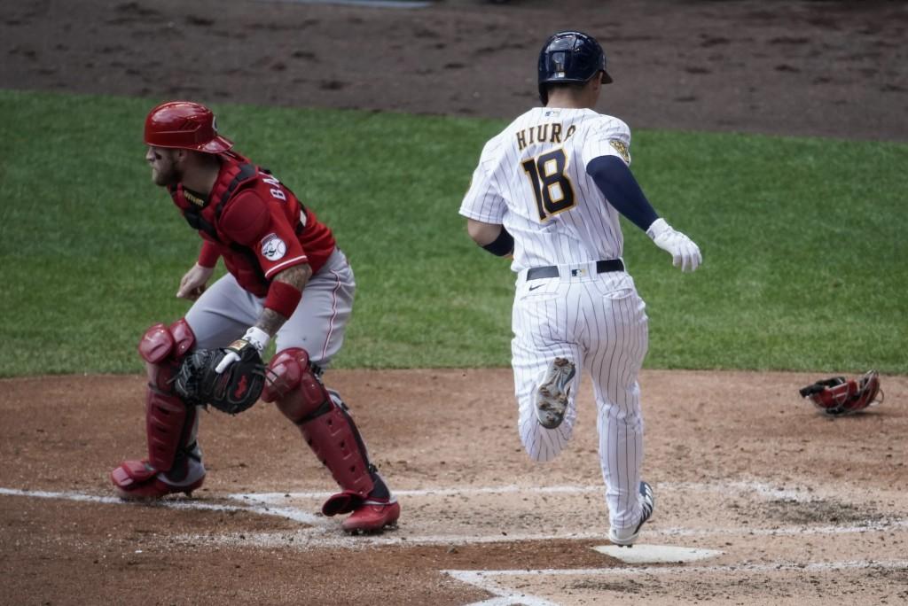 Milwaukee Brewers' Keston Hiura scores past Cincinnati Reds catcher Tucker Barnhart during the third inning of a baseball game Sunday, Aug. 9, 2020, i...