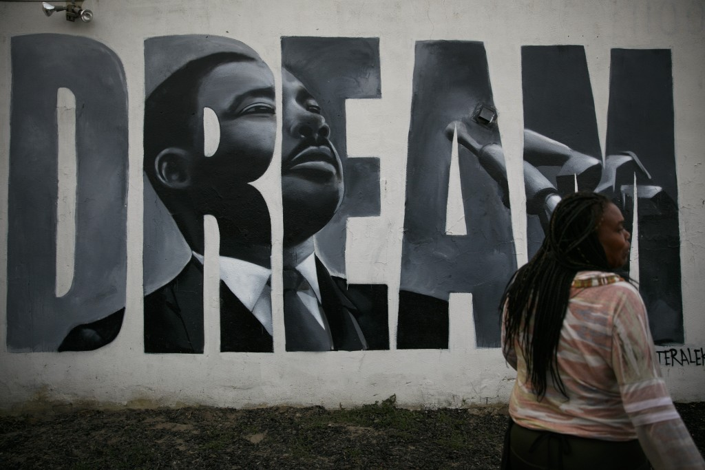 Lorinda Lacy, 45, stands outside her party store painted with a mural depicting Martin Luther King Jr. in the Watts neighborhood of Los Angeles, Tuesd...