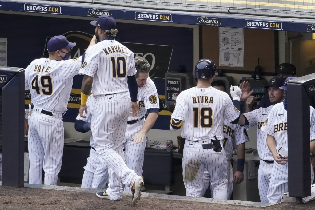 Milwaukee Brewers' Keston Hiura (18) is congratulated after hitting a home run during the seventh inning of a baseball game Sunday, Aug. 9, 2020, in M...