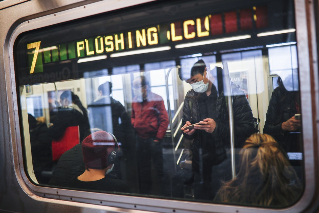 FILE - In this April 7, 2020, file photo, some people wear masks while using the New York City subway system during the coronavirus pandemic in New Yo...