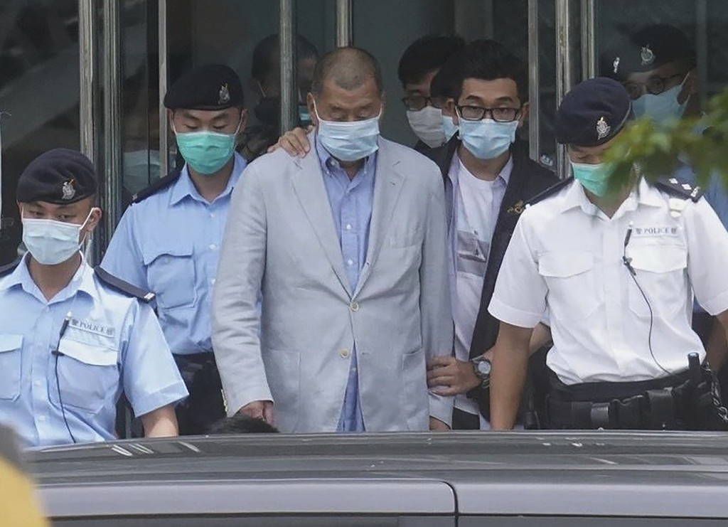 Hong Kong media tycoon Jimmy Lai, center, who founded the local newspaper Apple Daily, is escorted by police from the leave the Apple Daily headquarte...
