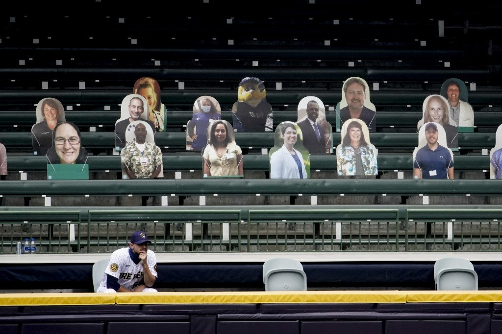 Milwaukee Brewers relief pitcher Justin Grimm watches from the makeshift bullpen during the third inning of a baseball game against the Cincinnati Red...