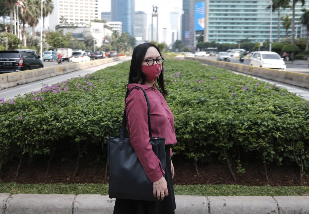 Clara Karina poses for a photo as she waits to cross a road after a job interview at the main business district in Jakarta, Indonesia, Thursday, Aug. ...