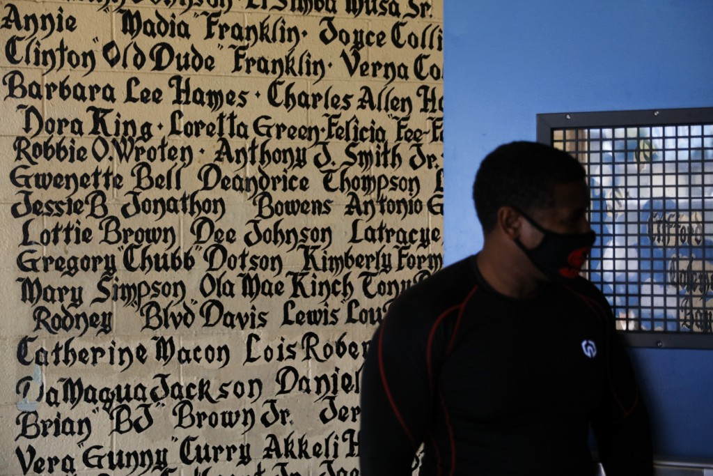 Volunteer Kevin Hunt stands against a wall bearing the names of tenants, who died while living in the Nickerson Gardens housing project, in the Watts ...
