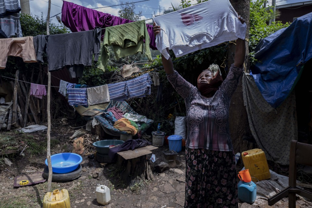 Mother of two Amsale Hailemariam, a domestic worker who lost work because of the coronavirus, hangs clothes after washing them outside her small tent ...
