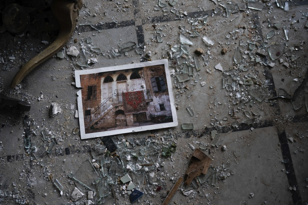 A photo rests among broken glass on the floor of the Sursock Palace, heavily damaged after the explosion in the seaport of Beirut, Lebanon, Friday, Au...