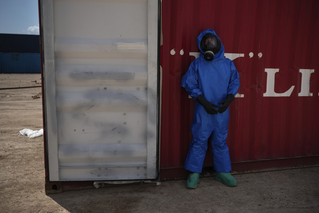 A French emergency worker, part of a special unit working with chemicals, stands next to a shipping container storing flammable liquids, at the site o...