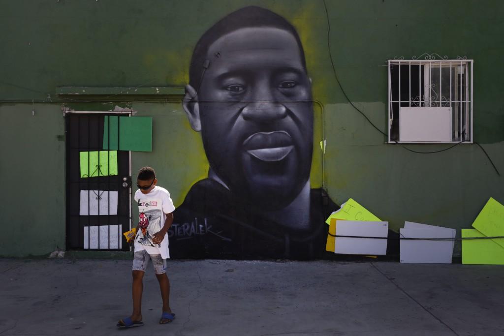 Benjamin Jackson III, 10, walks past a mural depicting George Floyd in the Watts neighborhood of Los Angeles, Tuesday, June 9, 2020. There were no fir...