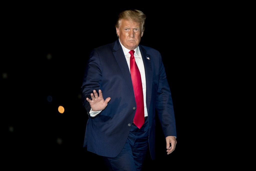 President Donald Trump waves to members of the media as he walks across the South Lawn as he arrives at the White House in Washington, late Sunday, Au...
