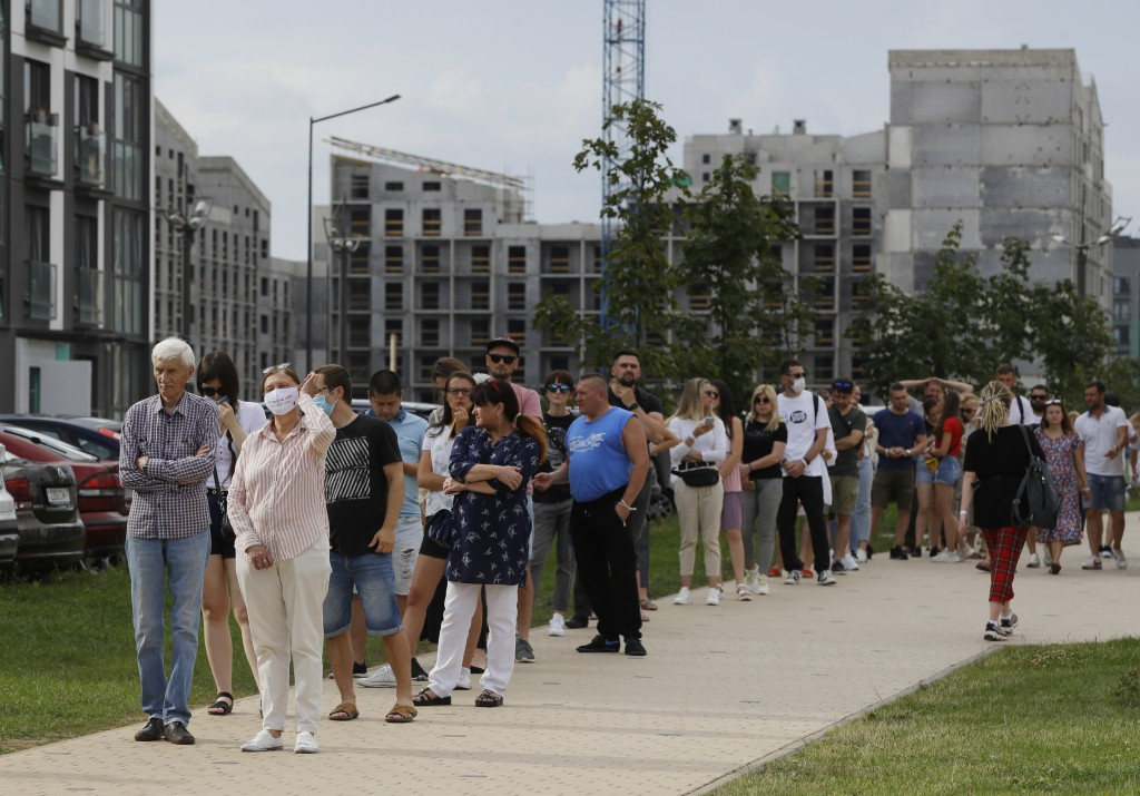 People queue to cast their votes in the Belarusian presidential election in Minsk, Belarus, Sunday, Aug. 9, 2020. Belarusians are voting on whether to...