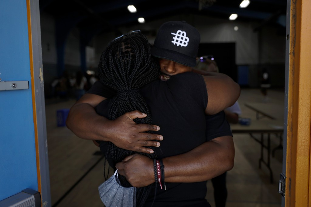 Think Watts Foundation's Sheldon Lewis, facing camera, hugs volunteer Tanya Dorsey after attending a community event held to give out free food to ten...