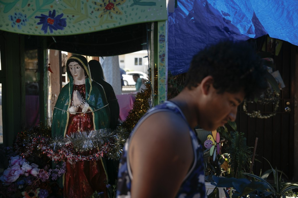 Noel Mata walks past a statue of Our Lady of Guadalupe made by his parents in the Watts neighborhood of Los Angeles, Monday, Aug. 3, 2020. Watts has c...