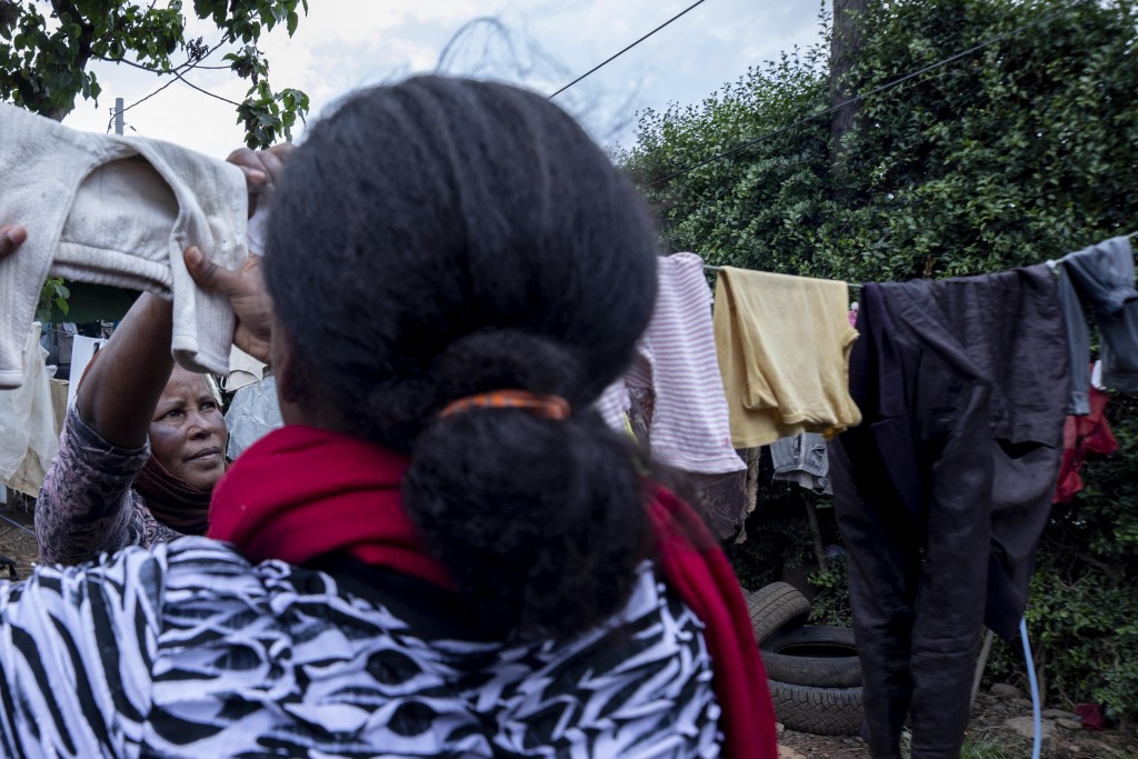 Mother of two Amsale Hailemariam, left, a domestic worker who lost work because of the coronavirus, hangs washing on the line with her daughter, Bethl...