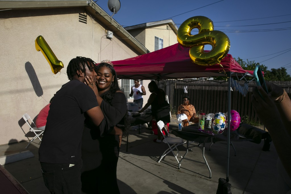 Kyaira Shaw gets a kiss from her boyfriend, Camari Baseer, left, while posing for photos at her 18th birthday party in the Watts neighborhood of Los A...