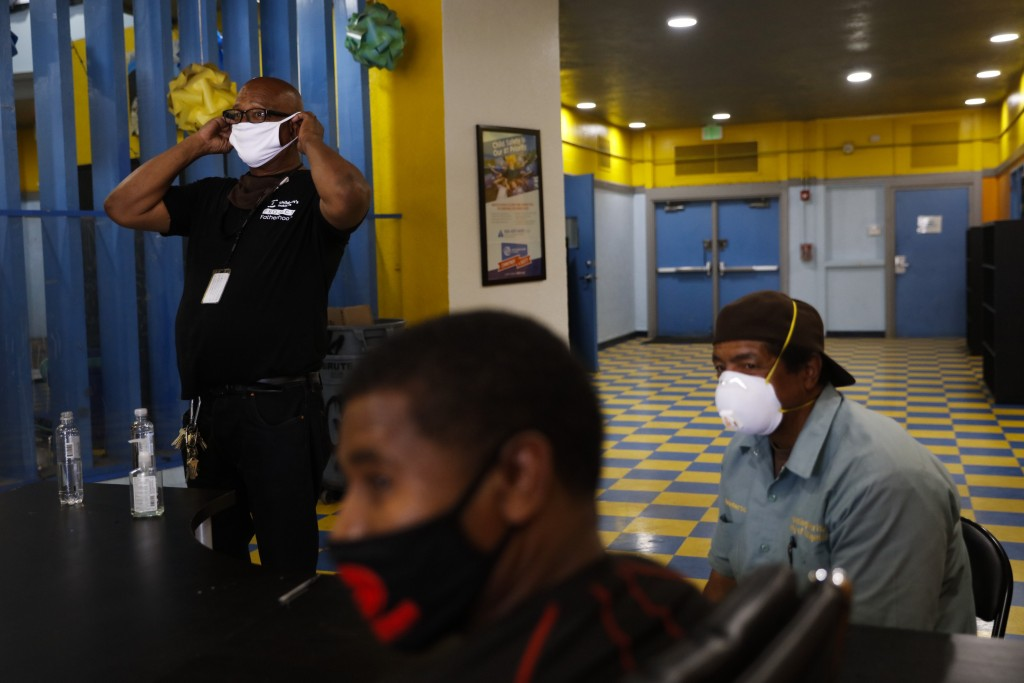 Donny Joubert, left, vice president of Watts Gang Task Force, puts on a face mask while waiting for volunteers to arrive before a community event as h...