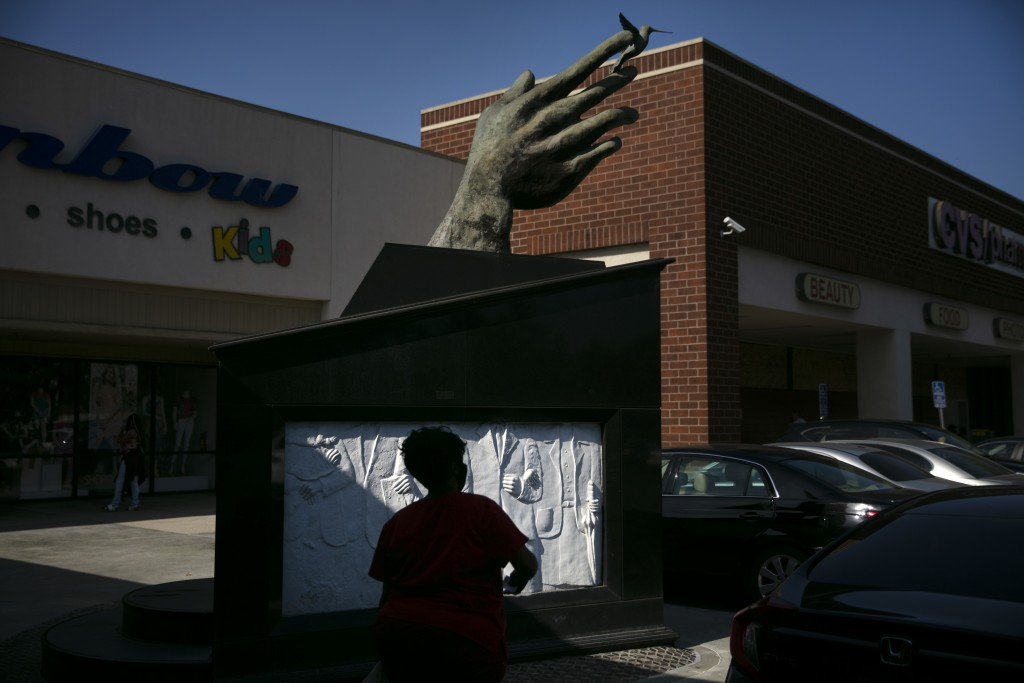 A shopper walks past a sculpture built in 1992 to honor Martin Luther King Jr. at a shopping mall named after Dr. King in the Watts neighborhood of Lo...