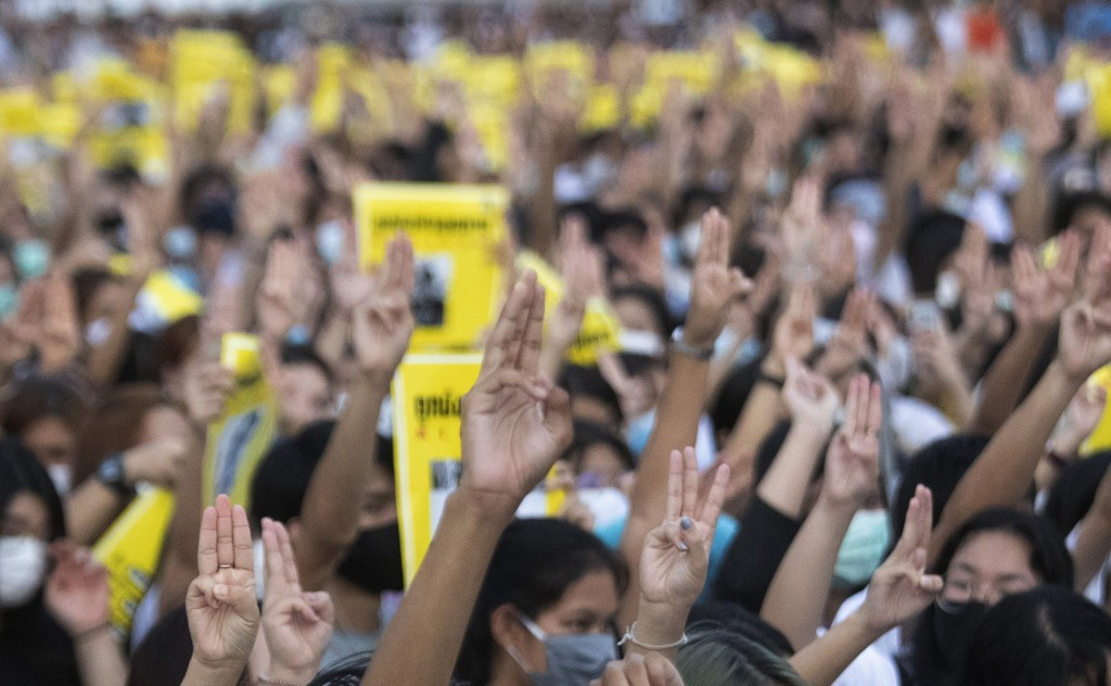 Pro-democracy students raise a three-finger symbol of resistance salute during a protest at the Thammasat University in Pathum Thani, north of Bangkok...
