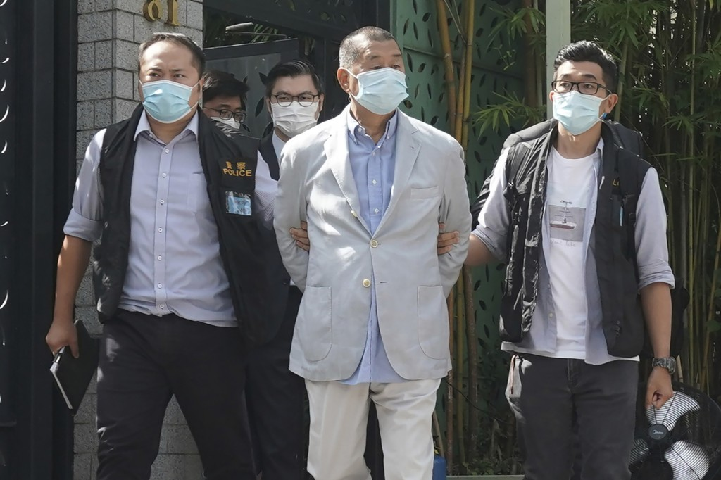 Hong Kong media tycoon Jimmy Lai, center, who founded local newspaper Apple Daily, is arrested by police officers at his home in Hong Kong, Monday, Au...