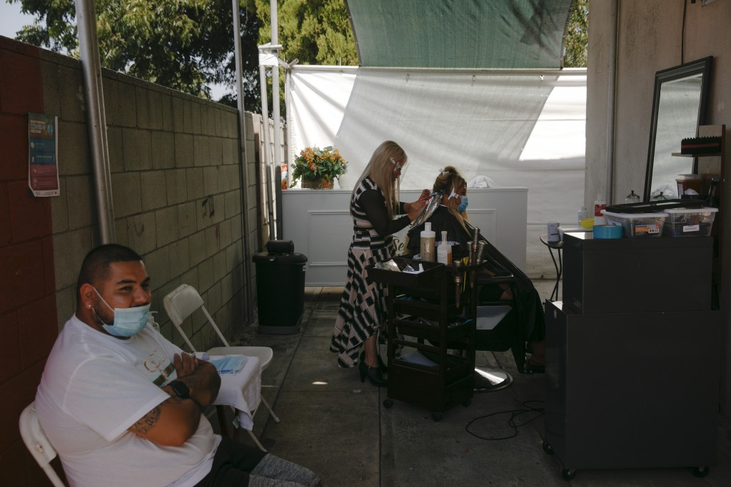Mario Perez, 32, left, sits on a chair while his wife, Jocelyn, gets her hair bleached at an outdoor hair salon in the Watts neighborhood of Los Angel...