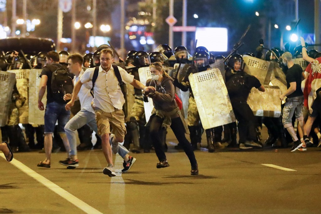 Demonstrators run away from police as they gather to protest against a result of the Belarusian presidential election in Minsk, Belarus, Sunday, Aug. ...