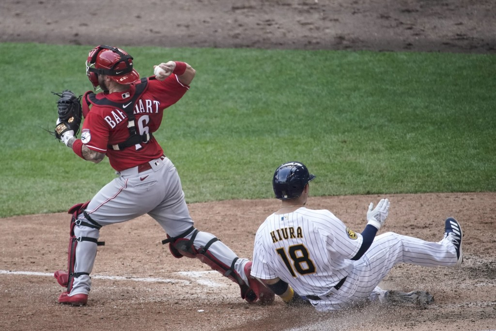 Milwaukee Brewers' Keston Hiura is forced out at home as Cincinnati Reds catcher Tucker Barnhart makes a late throw at first during the sixth inning o...