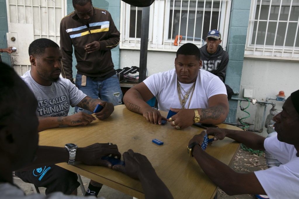 Tenants play dominoes outside an apartment building at the Imperial Courts housing project in the Watts neighborhood of Los Angeles, Wednesday, June 1...