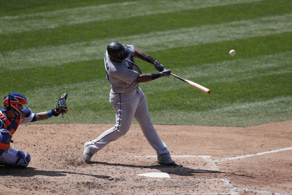 Miami Marlins' Jesus Aguilar, right, hits a fifth-inning solo home run during a baseball game against the New York Mets at Citi Field, Sunday, Aug. 9,...