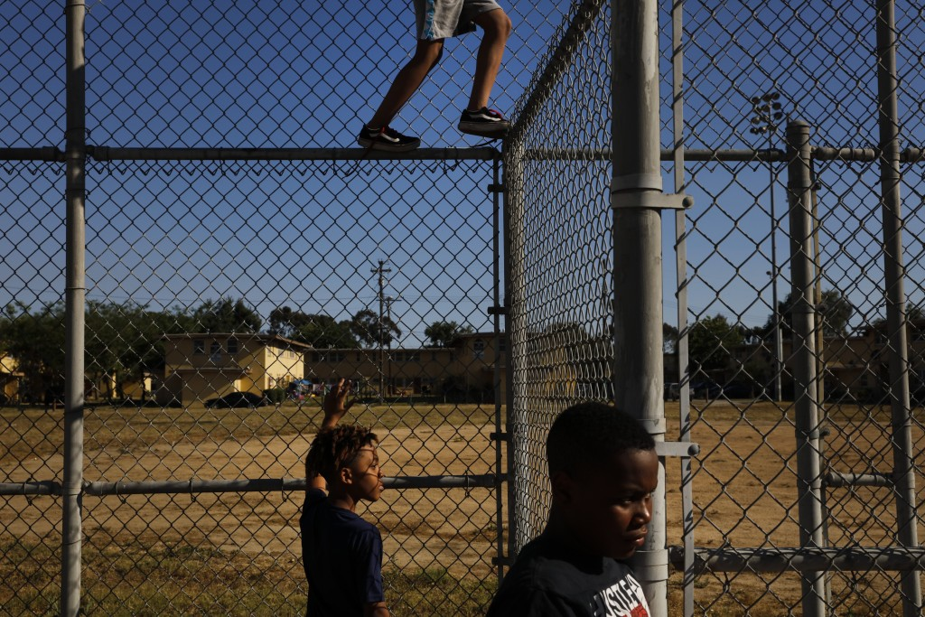 Three boys pass time in an empty playground at the Nickerson Gardens housing project in the Watts neighborhood of Los Angeles, Wednesday, June 10, 202...