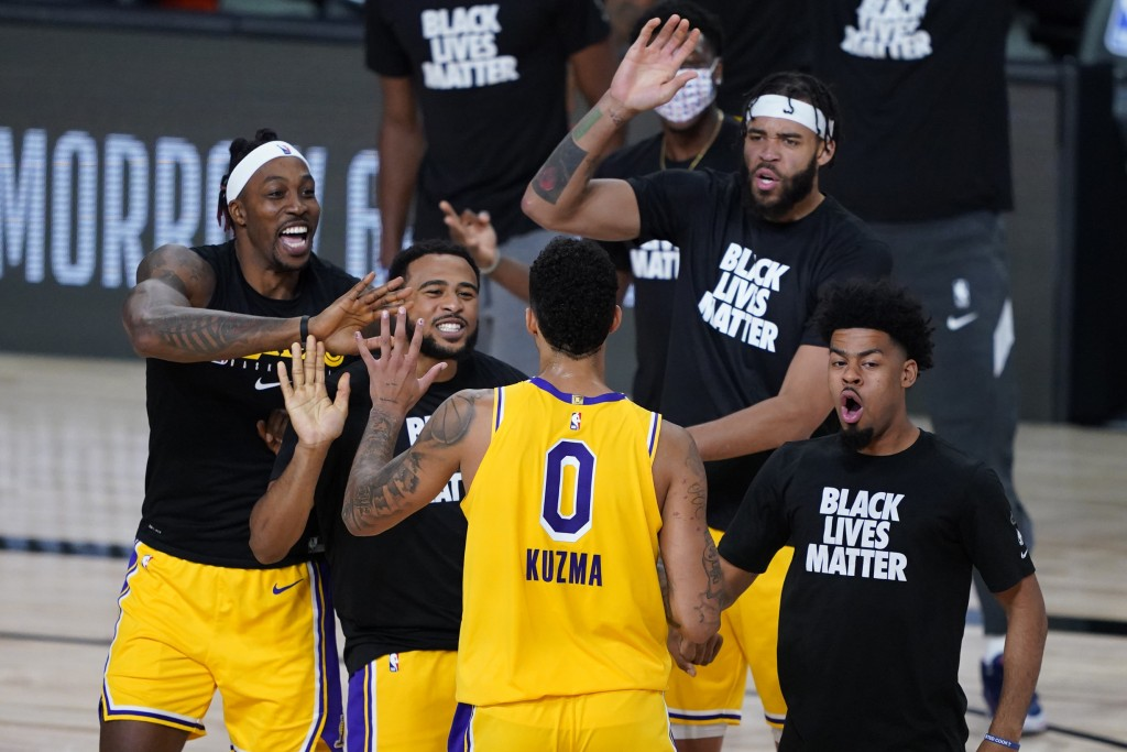 Los Angeles Lakers' Kyle Kuzma (0) is congratulated by teammates after hitting a game-winning 3-pointer against the Denver Nuggets during the second h...