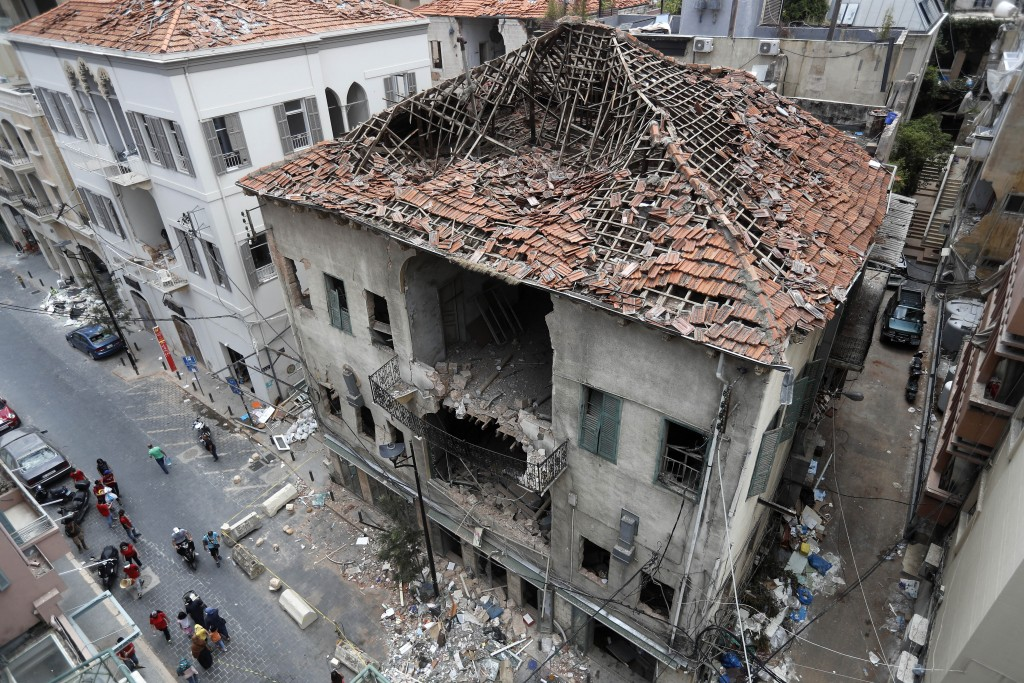 People pass in front of a house that was damaged during the last week's explosion that hit the seaport of Beirut, Lebanon, Tuesday, Aug. 11, 2020. (AP...