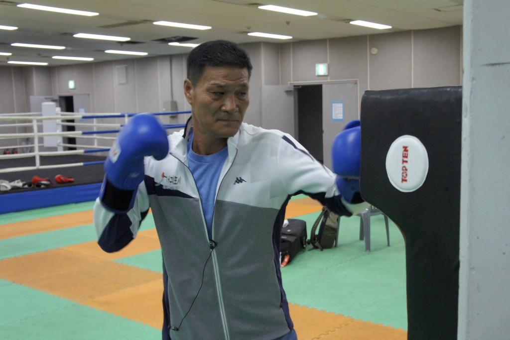 Former Olympic gold medalist Park Si-hun wearing boxing gloves punches a bag for photos after an interview on Jeju Island, South Korea, Tuesday, July ...