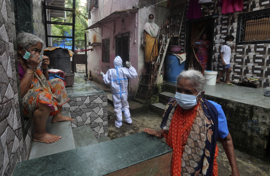 A health worker calls out to people to come out for screening for COVID-19 symptoms in Dharavi, one of Asia's biggest slums, in Mumbai, India, Tuesday...