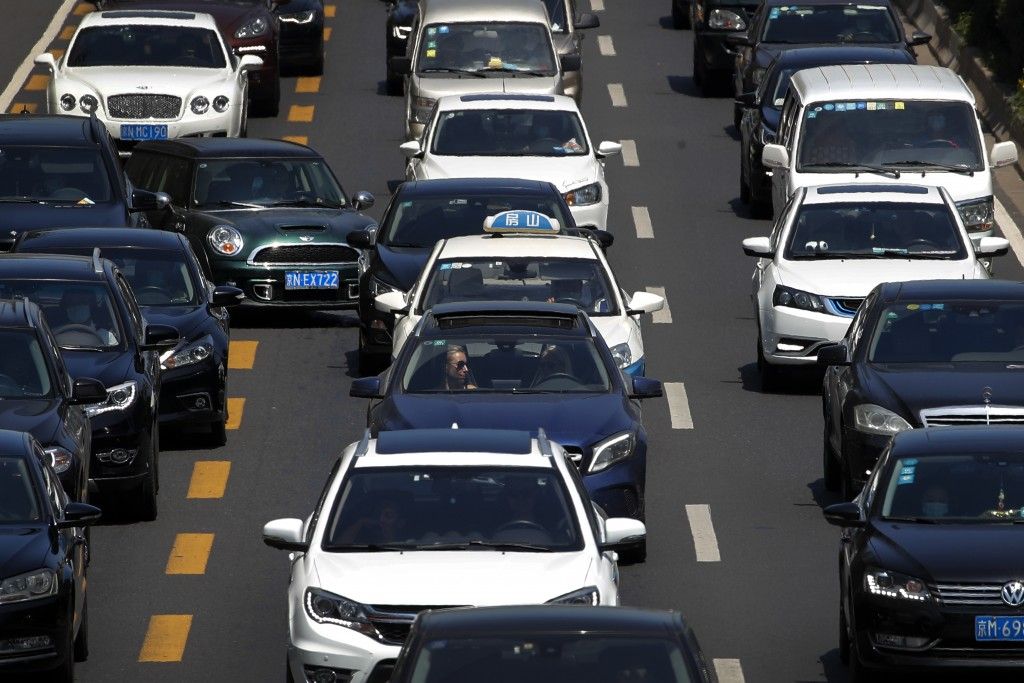 A motorist cuts into center lane as motorists clogged with heavy traffic on a city ring road in Beijing, Tuesday, Aug. 11, 2020. China's auto sales ro...