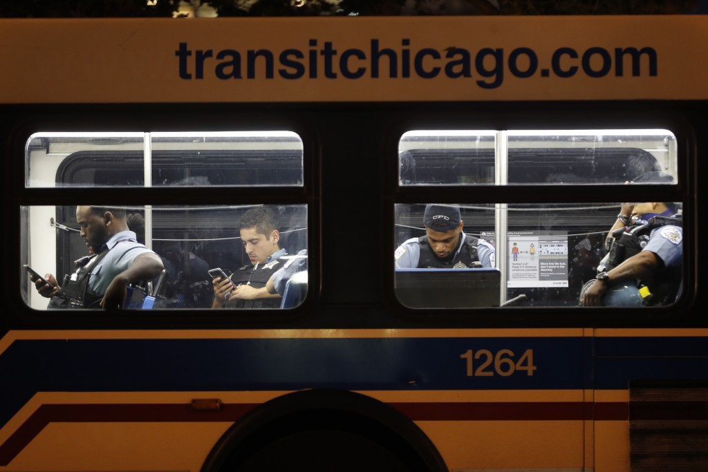 Chicago police officers wait on a transit bus Monday, Aug. 10, 2020, outside the Chicago Police Department's District 1 station in Chicago. (AP Photo/...