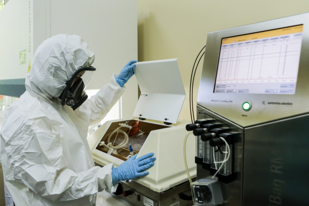 In this handout photo taken on Thursday, Aug. 6, 2020, and provided by Russian Direct Investment Fund, an employee works with a coronavirus vaccine at...