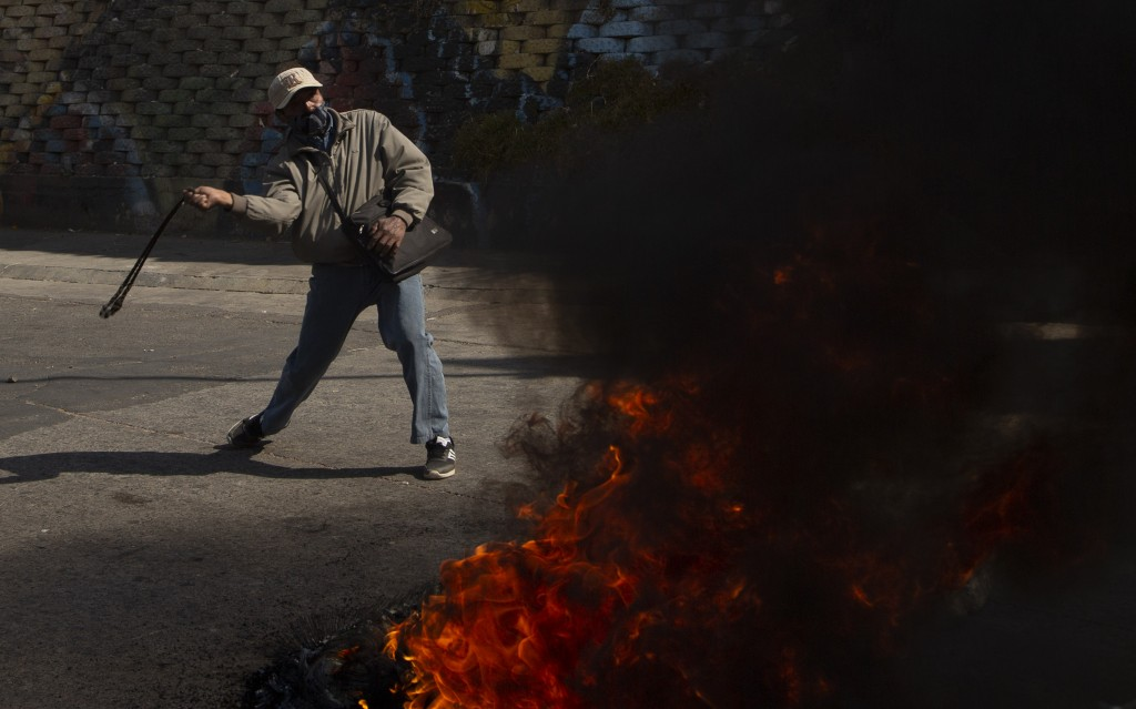 A demonstrator shows his slingshot as a message to police to not disperse a protest against the postponement of the presidential election in El Alto, ...