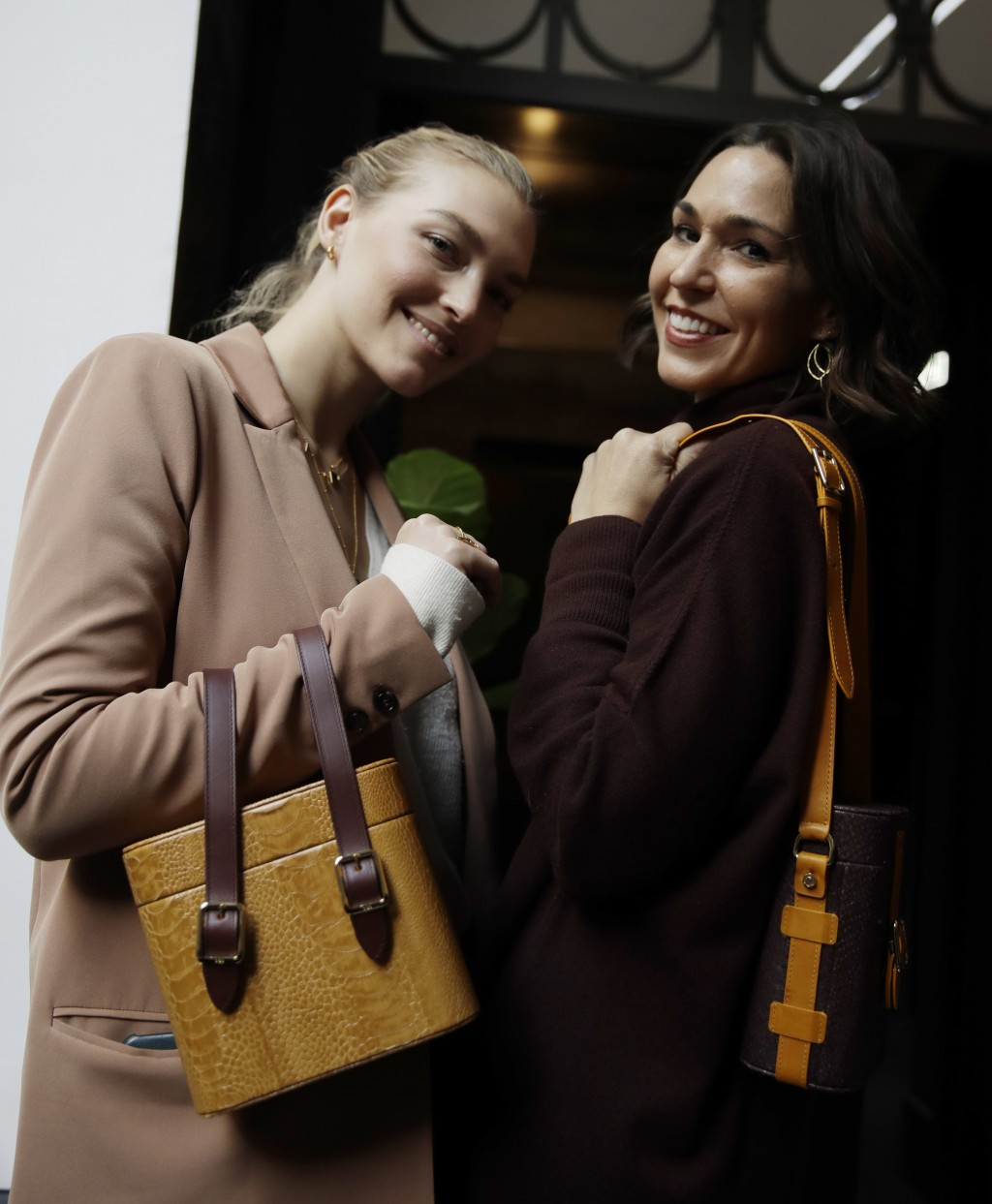 FILE - In this Feb. 24, 2019 file photo, model Arizona Muse, left, is flanked by designer and Officina del Poggio owner Allison Hoeltzel Savini as the...