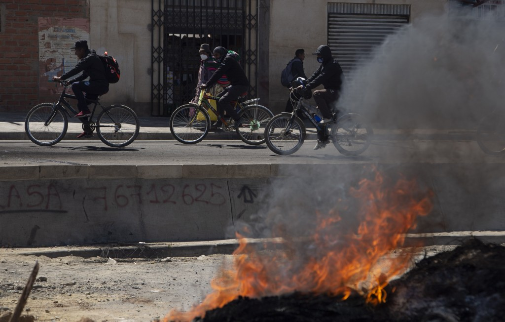 Commuters on bicycles ride past a barricade set up by protesters against the postponement of the presidential election in El Alto, Bolivia, Monday, Au...