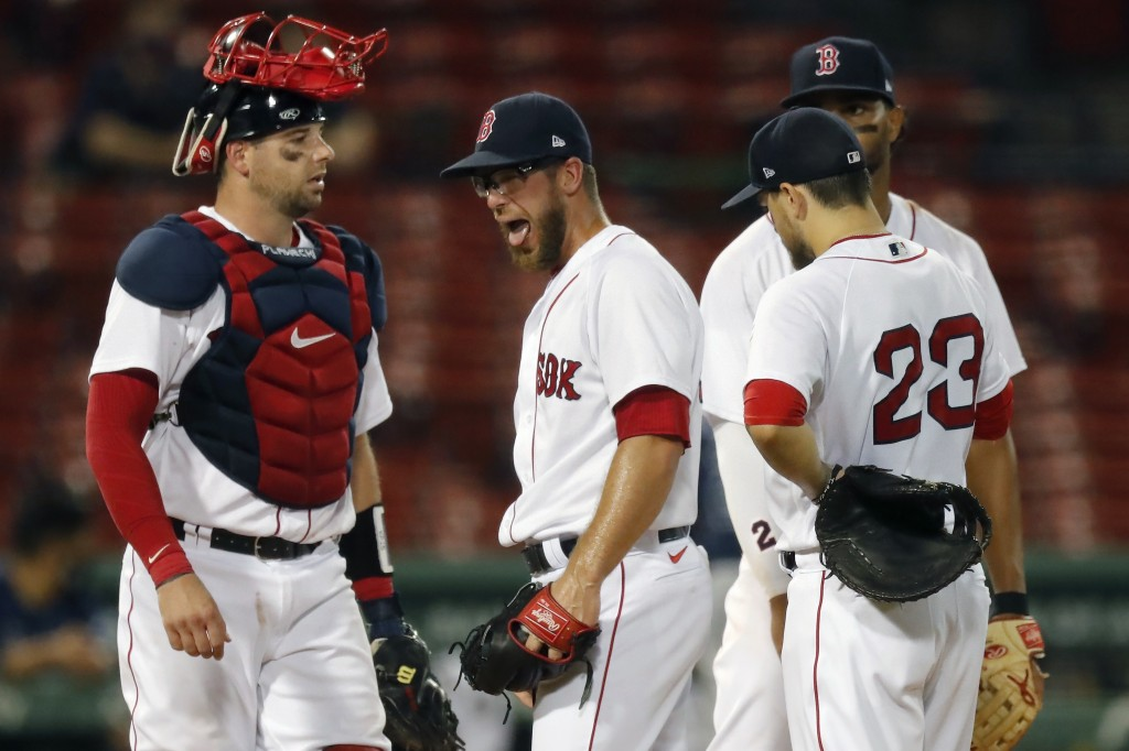 Boston Red Sox's Marcus Walden, center, reacts between teammates Kevin Plawecki, left, Xander Bogaerts, behind, and Michael Chavis (23) as manager Ron...