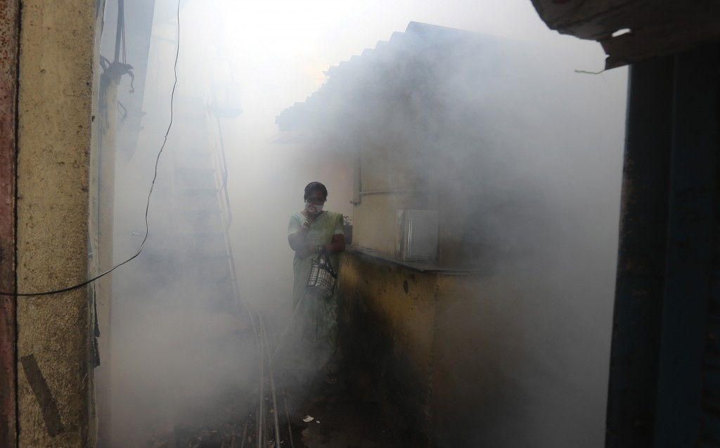 An Indian woman walks through a foggy lane as health workers fumigate the vicinity with anti-mosquito spray, in  Mumbai, India, Tuesday, Aug. 11, 2020...