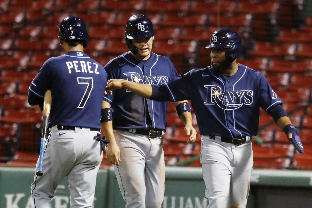 Tampa Bay Rays' Yoshitomo Tsutsugo, center, and Manuel Margot, right, walk to the dug out past Michael Perez (7) after scoring on a two-run double by ...
