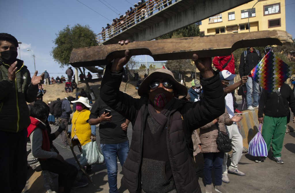Demonstrators wearing face masks amid the COVID-19 pandemic protest the postponement of the upcoming presidential election in El Alto, Bolivia, Monday...