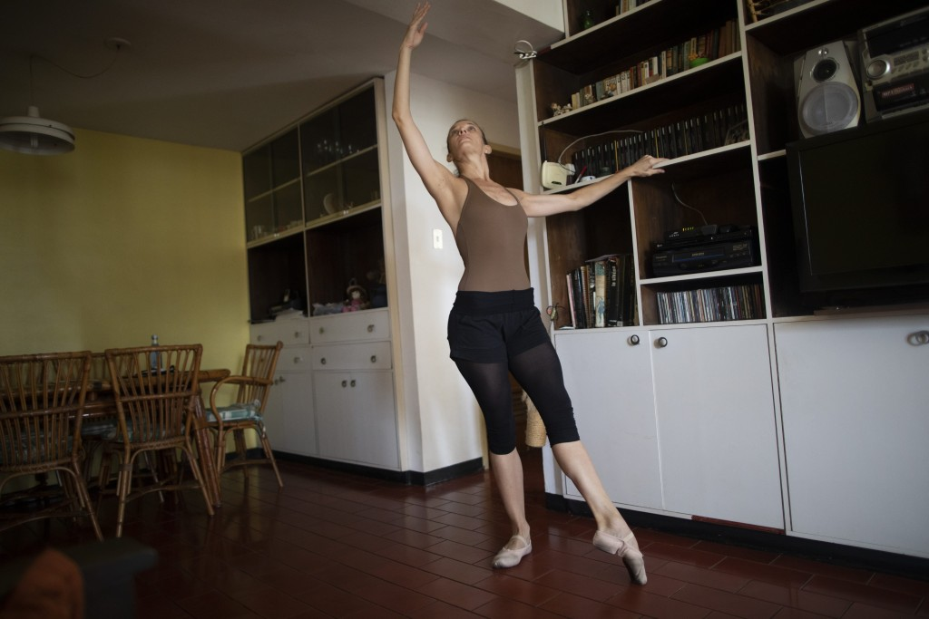 Carolina Wolf, who dances with Venezuela's national ballet, trains in her living room where she adapted her bookshelf to take the place of her ballet ...